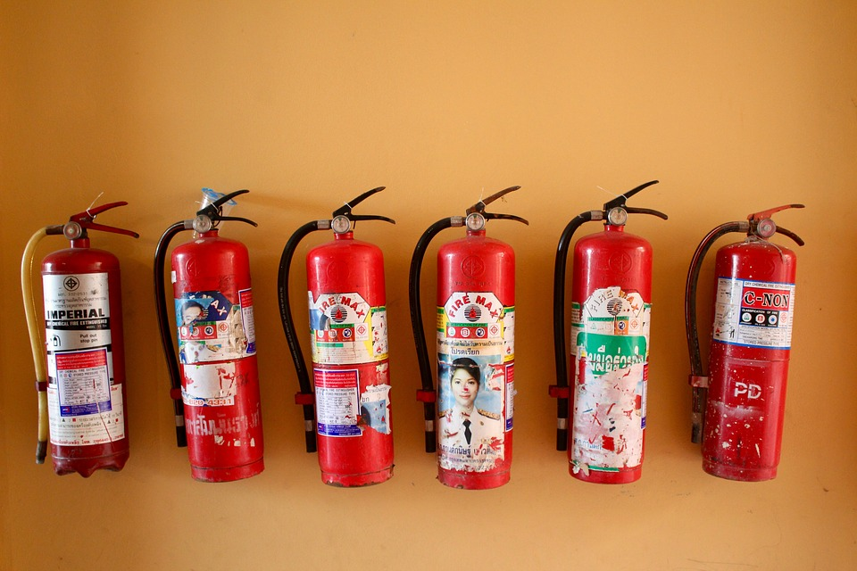 Fire extinguishers lined up on a wall